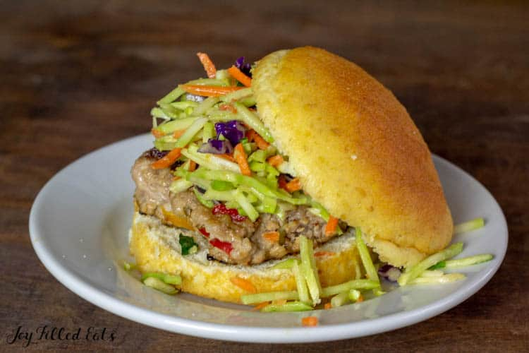 one of the asian burgers with broccoli slaw on a plate on a low carb bun