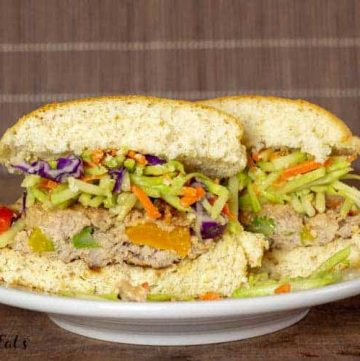 asian burger with broccoli slaw cut in half on a plate