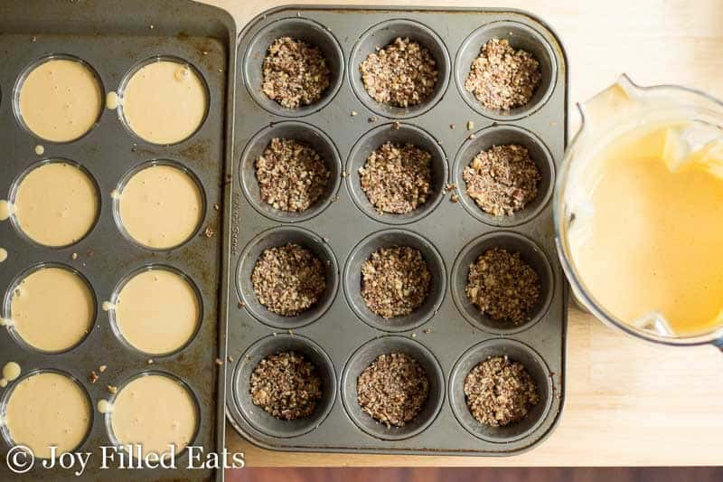 two muffin tins placed next to each other, one filled with pumpkin breakfast cheesecake batter and one lined with pecan crust, all next to a blender full of more cheesecake batter