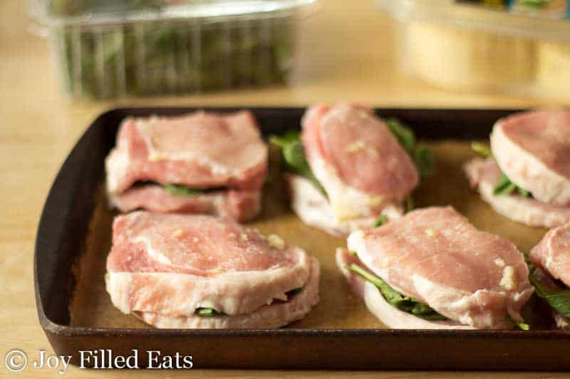 raw stuffed pork chops lined on a sheet pan before baking