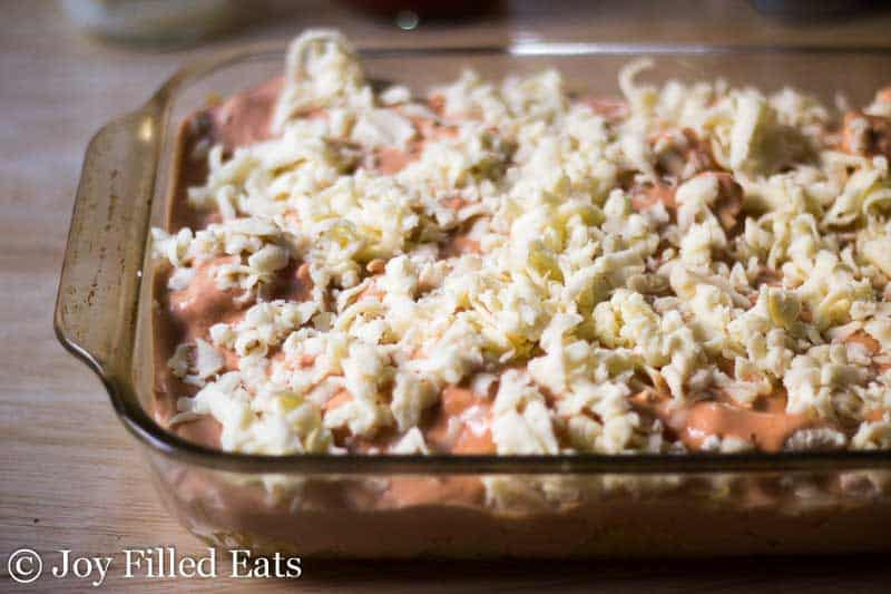 Creamy Tomato Chicken & Spaghetti Squash Casserole in a casserole dish with shredded cheese on top