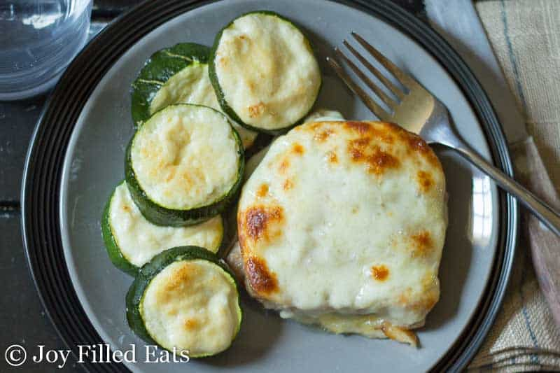 A cheesy stuffed pork chop and zucchini on a gray plate.