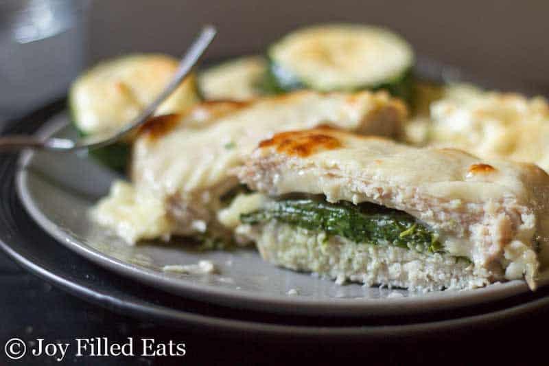 close up on halved stuffed pork chop on a light blue plate with fork