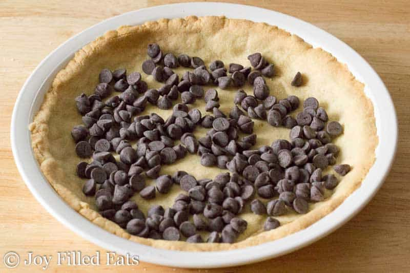 chocolate chips layered on top of a low carb keto pie crust in a white pie plate