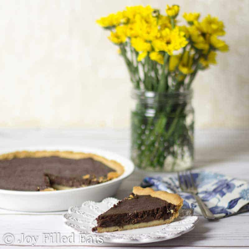 slice of fudge brownie pie on a white plate set next to a decorative blue napkin, vase of yellow flowers and fudge brownie pie in white pie plate