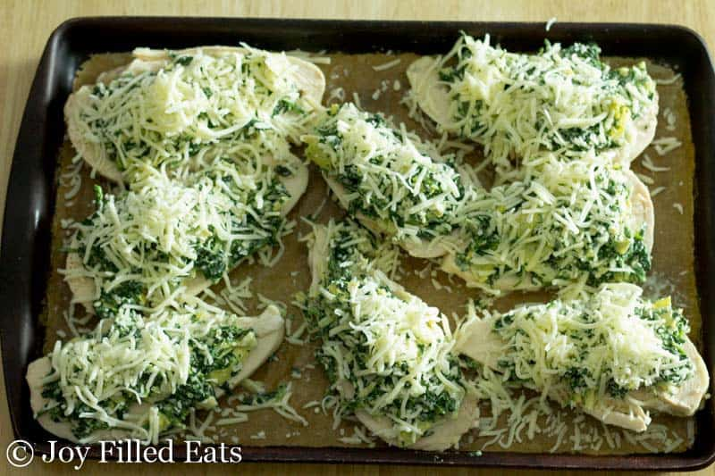 stoneware baking pan with cooked chicken breasts topped with spinach and cheese
