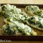 baking pan lined with cooked chicken pieces and topped with spinach, artichoke and melted cheese topping