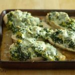 sheet pan lined with spinach artichoke chicken breasts