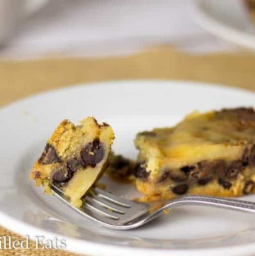 bite of sugar free vanilla fudge chocolate chip pie on a fork laying on a white plate with remaining slice of pie