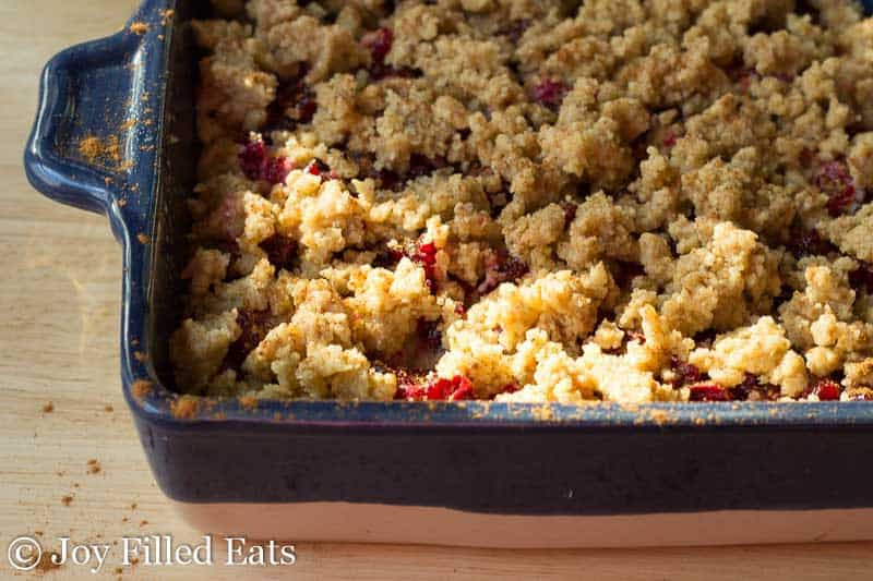 overhead view of cranberry walnut crumb cake on a blue and white casserole dish