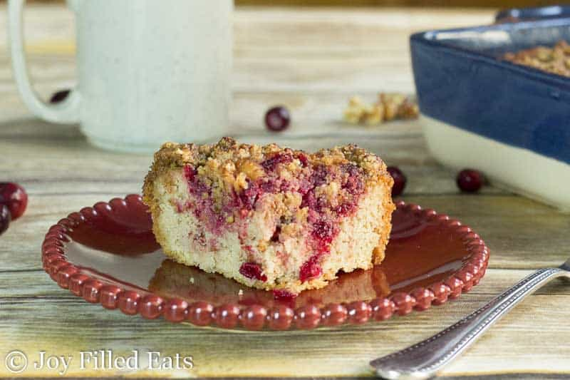 slice of cranberry walnut crumb cake on a red plate set on a wooden table
