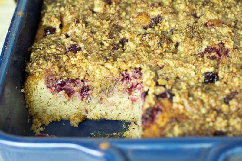 blue casserole dish filled with cranberry walnut crumb cake with corner slice missing