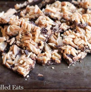 close up on pile of salted chocolate almond brittle bark on a wooden surface