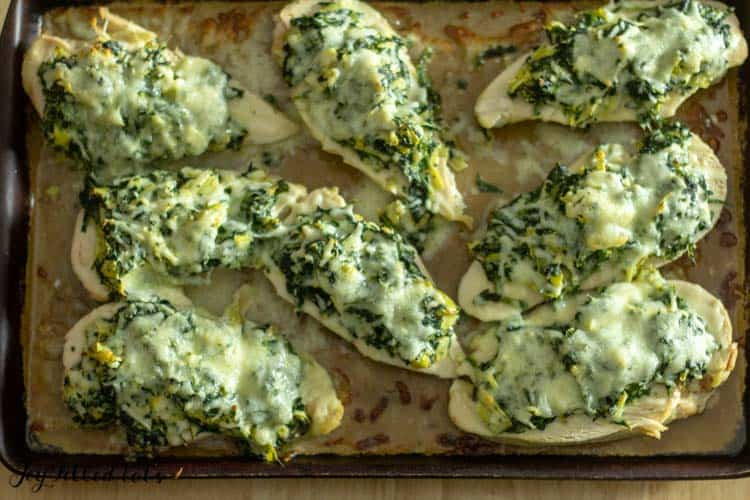 overhead shot of 8 pieces of Spinach Artichoke Chicken on a stoneware baking pan