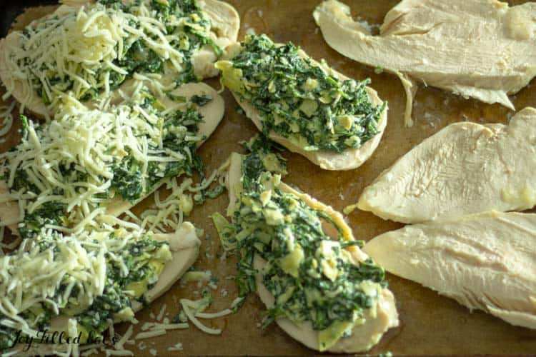 sheet pan with chicken breasts in different stages of assembling lazy spinach artichoke chicken breasts