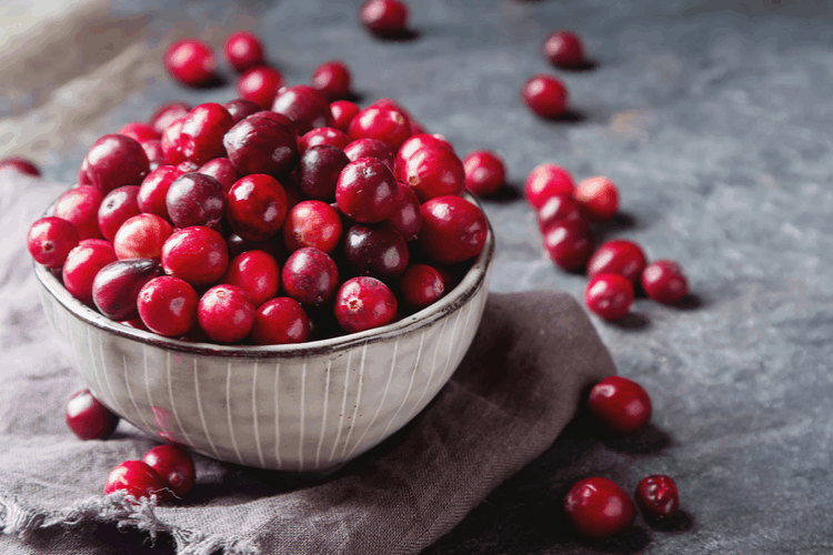 small bowl overflowing with cranberries, with many cranberries scattered around on surface