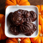 overhead view on pile of sugar free peanut butter pumpkins on a square white plate placed on mini pumpkins