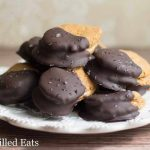 large pile of chocolate dipped peanut butter sandwich cookies on a white plate