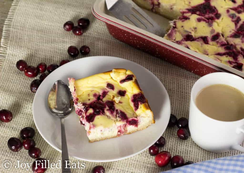 square piece of cranberry swirl cheesecake bars with a spoon on a plate next to a white mug of coffee
