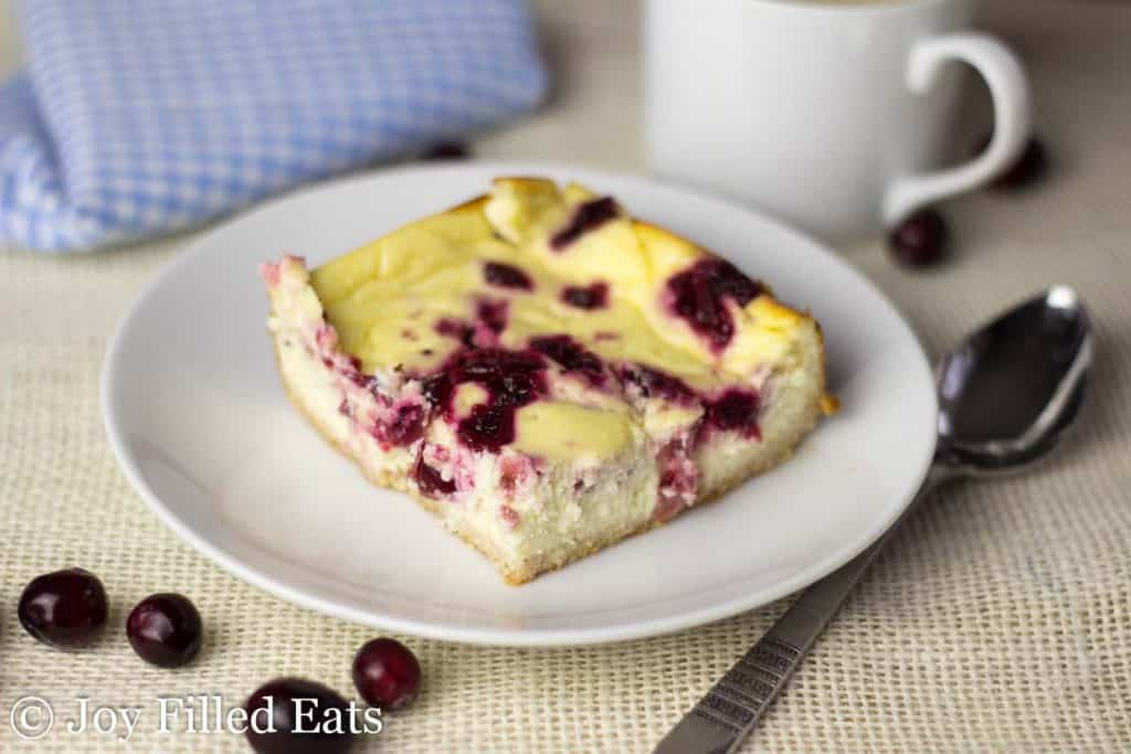 square piece of cranberry swirl cheesecake bar on a white plate next to a spoon and scattered cranberries