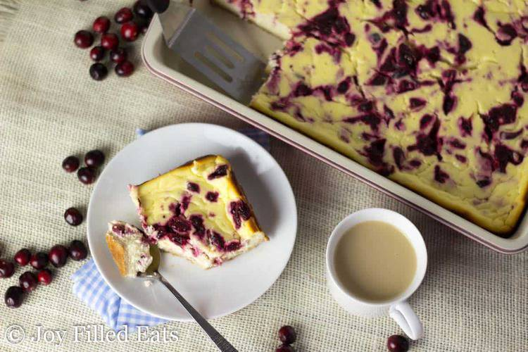 square piece of cranberry swirl cheesecake bars broken up with a spoon next to a mug of coffee and casserole dish with more cranberry cheesecake bars