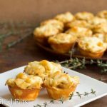 three onion tartlets arranged on a white plate with a sprig of thyme next to a platter of more french onion tartlets