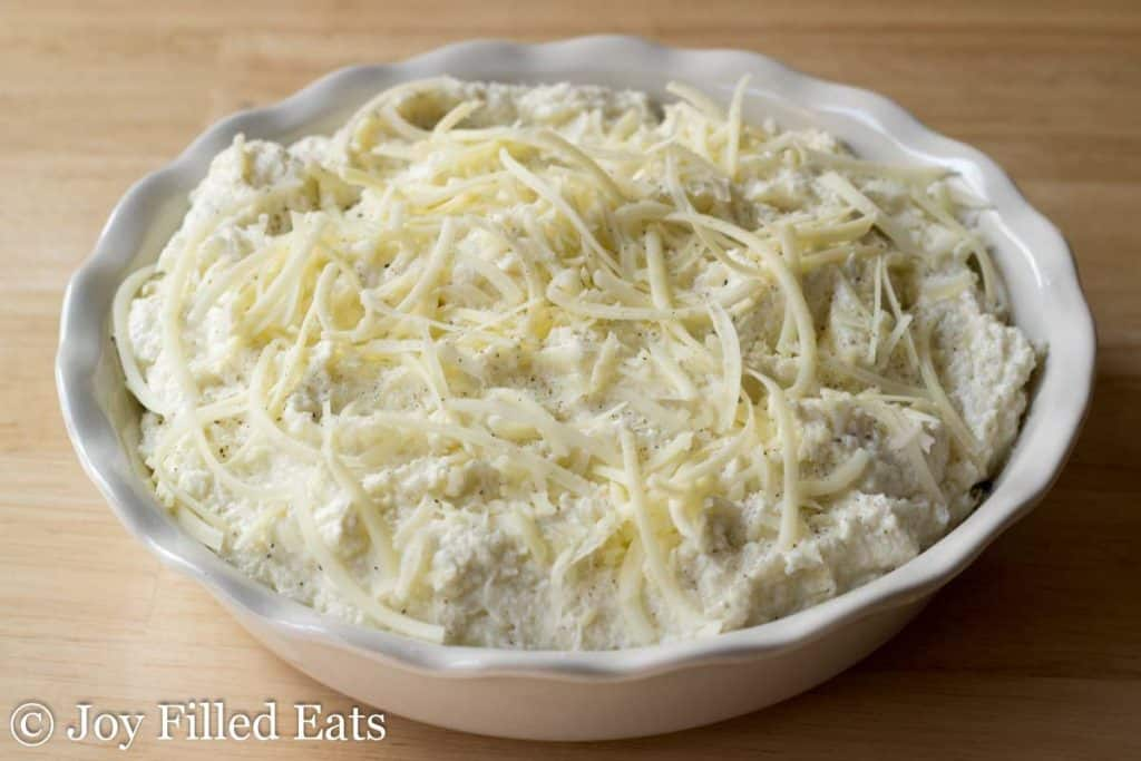 pie plate of mashed cauliflower with shredded cheese
