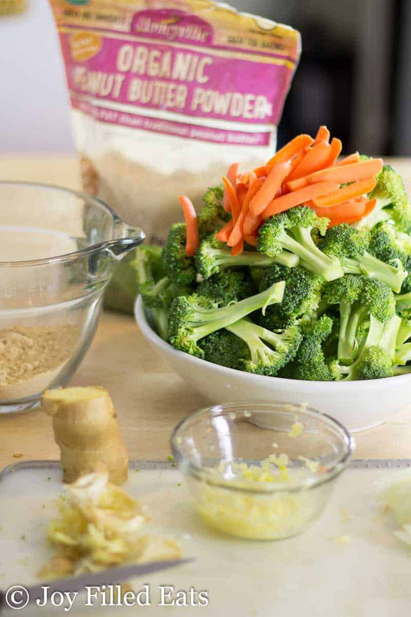 bowl of broccoli florets and sliced carrots next to a small dish of grated ginger and a package of organic peanut butter powder
