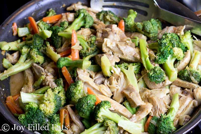 overhead view of skillet filled with chicken, broccoli and carrots