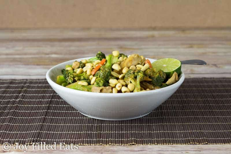 thai peanut chicken and broccoli in a white bowl set on a rustic place mat