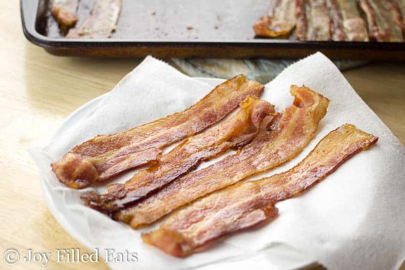 strips of bacon laying on a paper towel covered plate