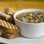 small white bowl of sausage and kale soup on a white plate with a panini sandwich