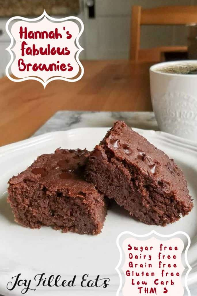 Brownies stacked on a white plate on a wooden table with a mug of coffee in the background
