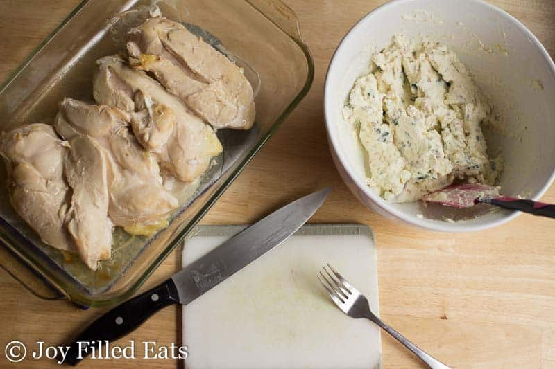 Getting ready for the the preparation for this Jalapeno Popper Chicken Casserole. Cooked chicken in a casserole dish and the cream cheese topping in a white bowl. Cutting board with a knife and fork in the foreground.
