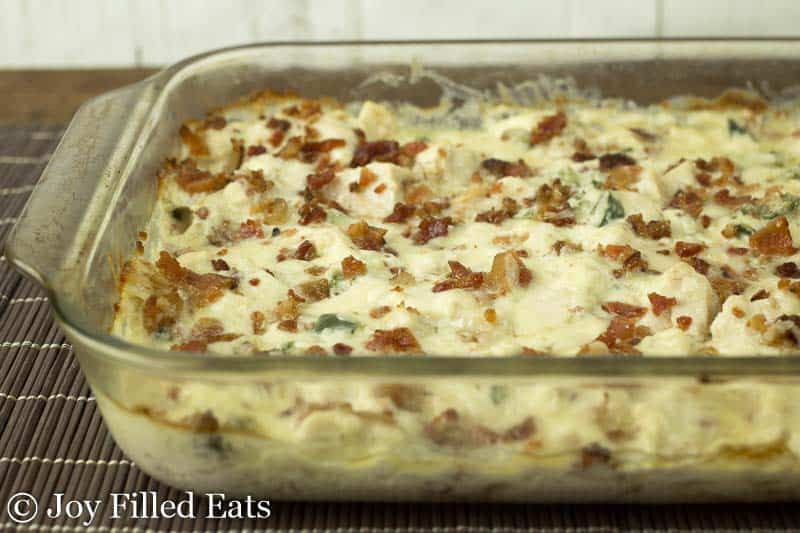 The baked jalapeno popper chicken casserole in a glass baking dish on a bamboo placemat