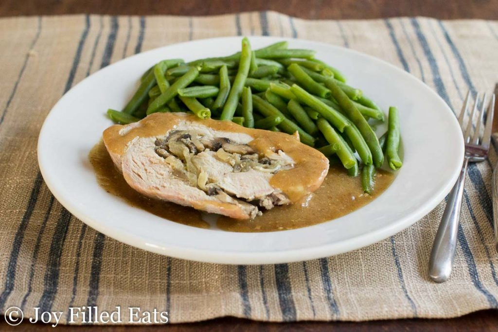plate of stuffed pork marsala covered in gravy with a side of green beans. Plate is accompanied by a fork and knife on a decorative place mat
