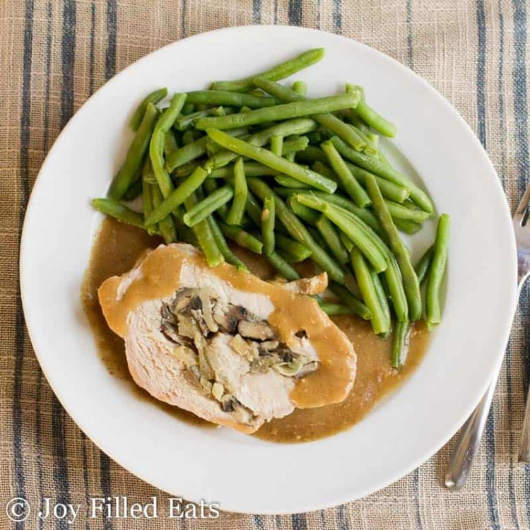 close up on overhead view of white plate with slice of stuffed pork marsala covered in gravy next to a side of green beans placed next to a fork and knife