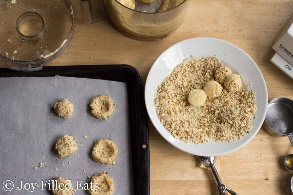 cookie dough balls placed in a bowl of chopped almond pieces next to a sheet pan with cookie dough balls and thumbprint shaped cookie dough