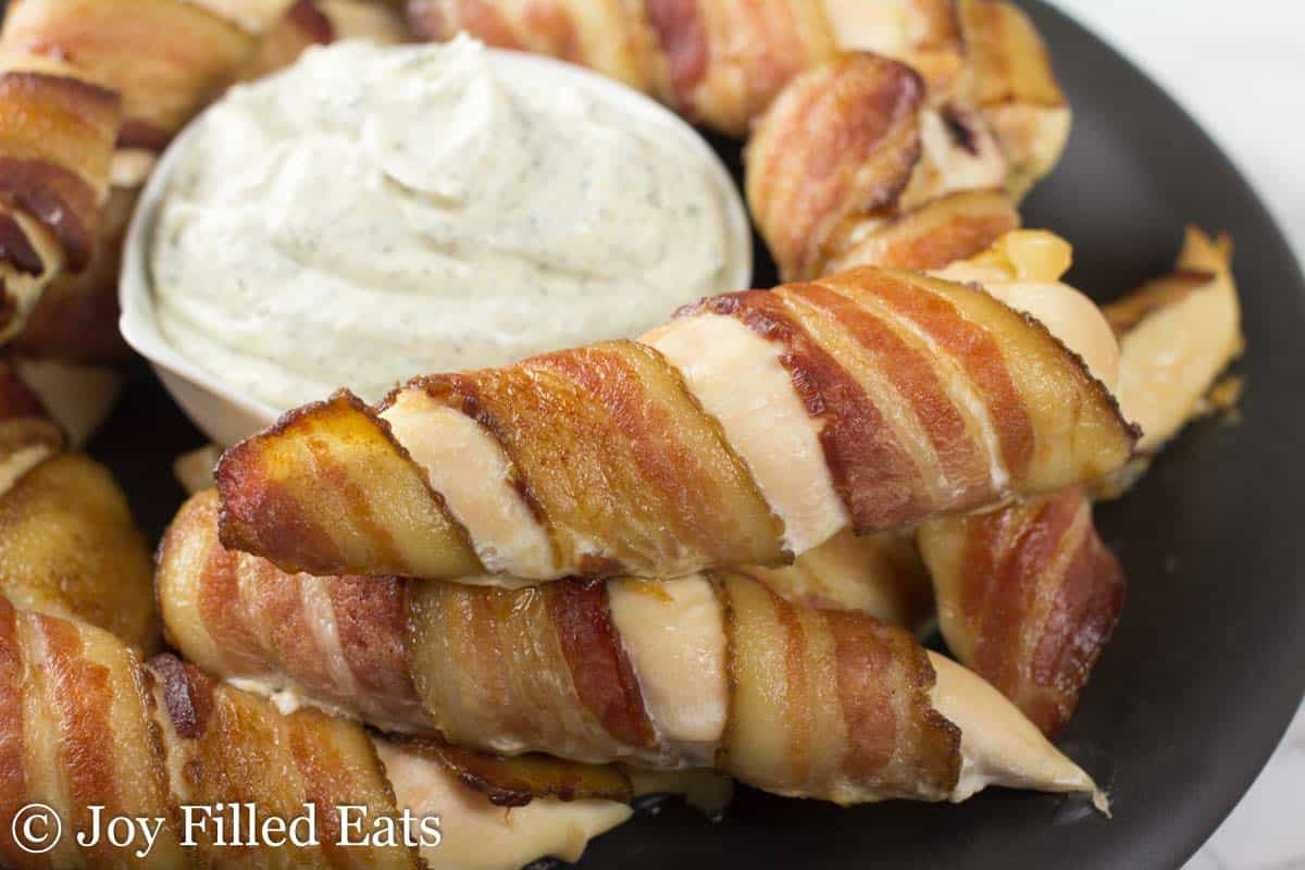 close up on bacon wrapped chicken tenders next to a small dish of ranch dip