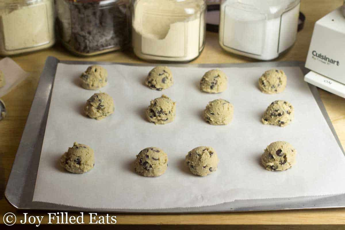 thin cookie pan covered in parchment paper and lined with chocolate chip cookie dough balls