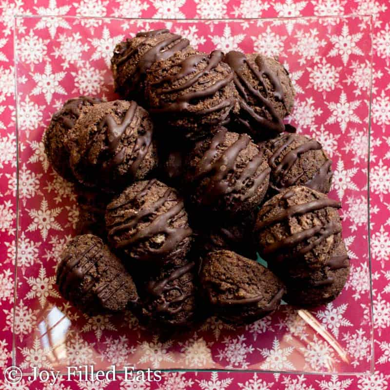 pile of chocolate chip mocha cookies on a glass plate set on a decorative pink table cloth