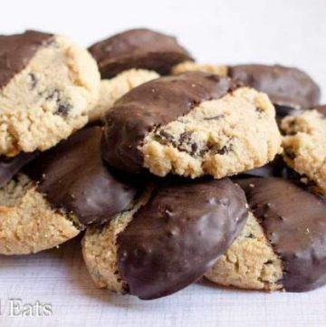 close up on pile of chocolate chip shortbread cookies, all half dipped in chocolate