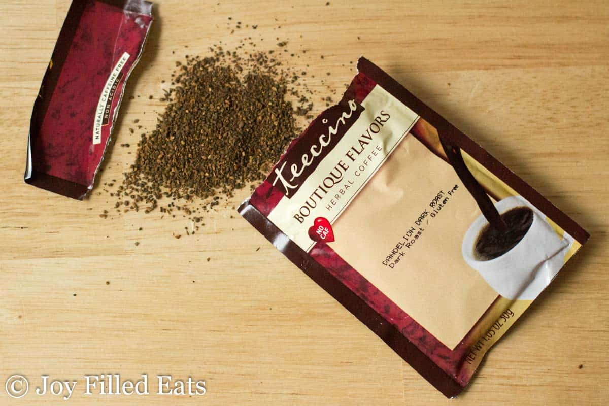 herbal coffee packet ripped open with coffee grounds spread on table