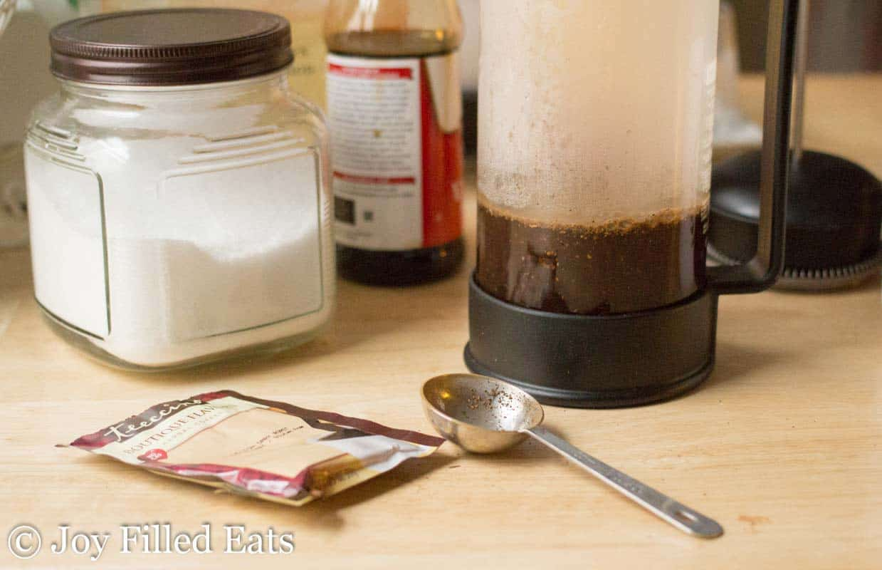 french press of coffee next to tablespoon and herbal coffee packet