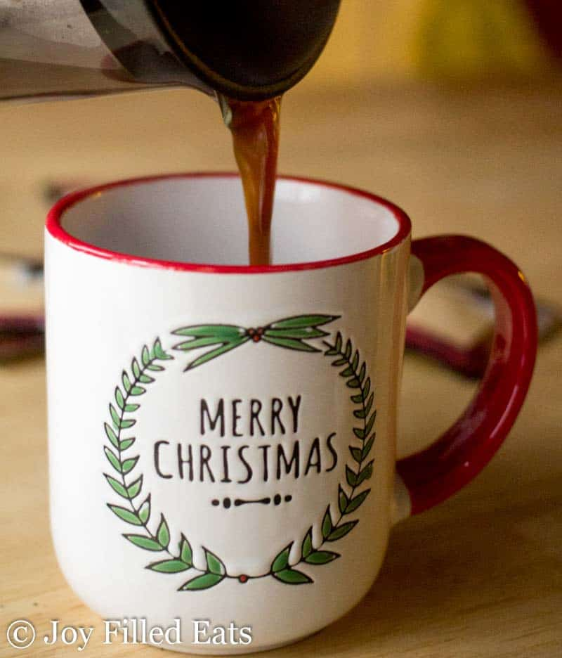 herbal coffee being poured into a 'Merry Christmas' decorative mug