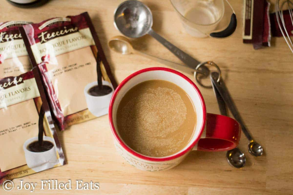 overhead view of coffee mug filled with cinnamon vanilla latte and surrounded by herbal coffee packets and kitchen utensils