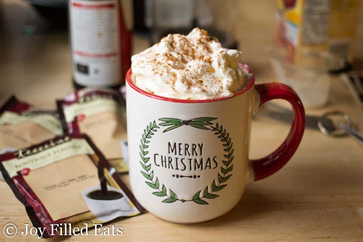 white mug reading 'Merry Christmas' with a red handle full of cinnamon vanilla latte topped with whipped cream and cinnamon surrounded by herbal coffee packets