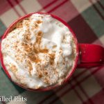 overhead view of cinnamon vanilla latte in a red mug topped with whipped cream