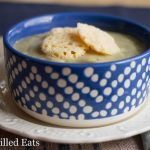 blue and white polka dot bowl filled with creamy garlic soup and topped with cheese croutons