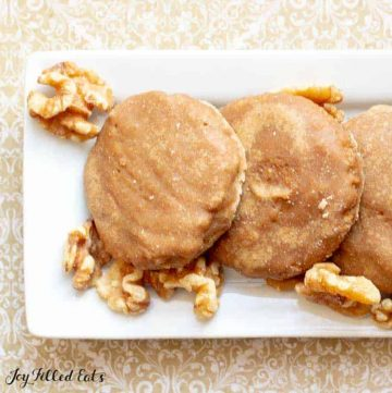 white, rectangular plate of glazed maple walnut cookies fanned out surrounded by whole, raw walnuts